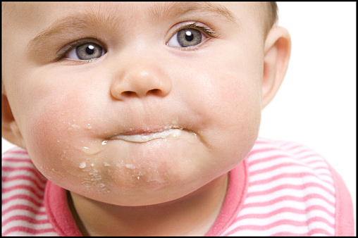Close-up of a baby with food on chin